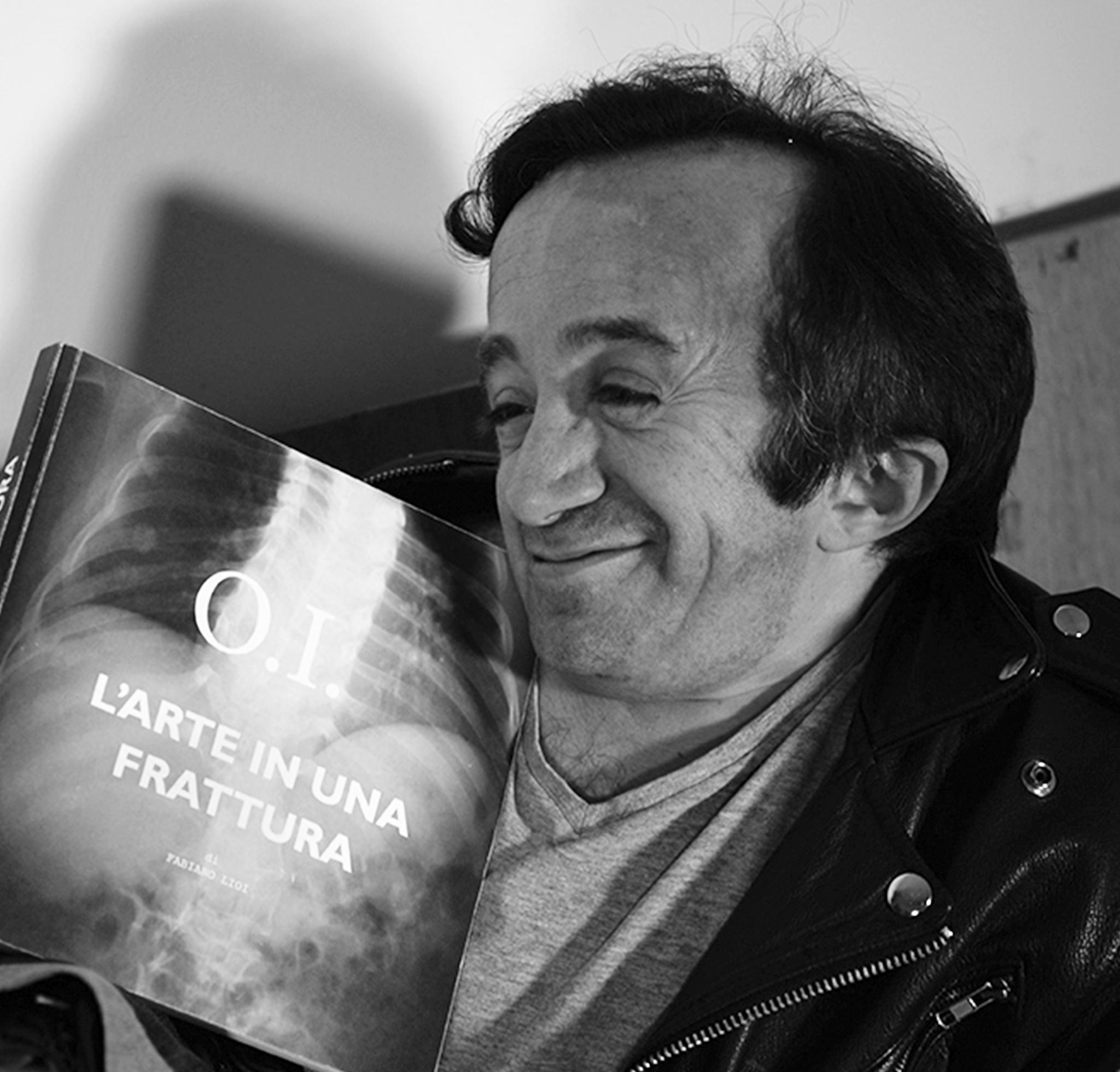 Fabiano Lioi Sorride con il suo libro O.I. L'arte in una frattura in mano, quasi sdraiato sulla sedia, e ti invita a leggere gli articoli del Blog!